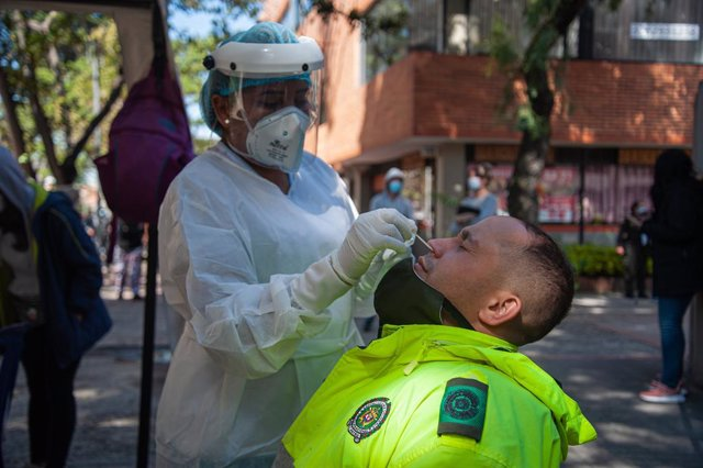 14 January 2021, Colombia, Bogota: A medical worker takes a nasal swab sample from a man during a free COVID-19 PCR test campaign. Photo: Chepa Beltran/VW Pics via ZUMA Wire/dpa