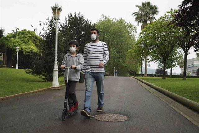 Un niño circula con un patinete junto a un adulto en el primer día en el que los menores de 14 años pueden salir a la calle, en Bilbao (País Vasco/España) a 26 de abril de 2020. Este domingo se ha comenzado a aplicar la medida de relajamiento del confinam