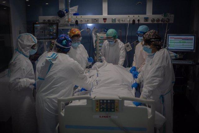 Trabajadores sanitarios protegidos atienden a un paciente en la Unidad de Cuidados Intensivos (Archivo)