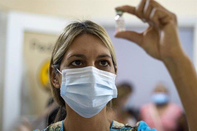 Una mujer observa un vial de la vacuna contra el coronavirus Sputnik V.
