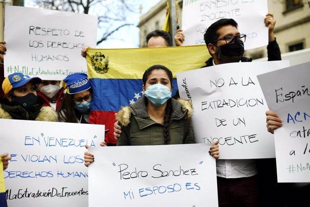 La mujer de Ernesto Quintero, el venezolano que fue detenido este miércoles por la Policía Nacional para ser extraditado a Venezuela, Cismary Marcano, sostiene una pancarta durante su visita al Tribunal Superior de Justicia Madrid para solicitar a las aut