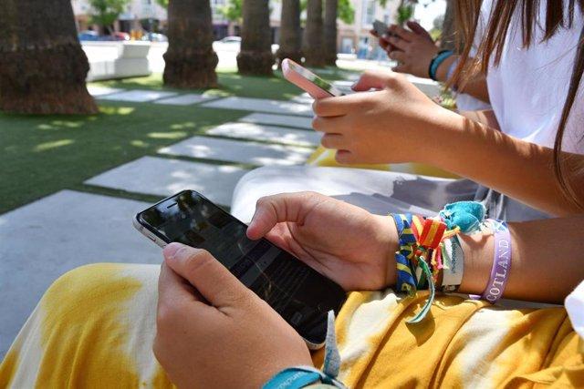 Jóvenes utilizando el movil en un parque de la localidad sevillana.