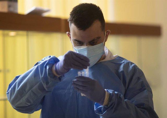 Un trabajador sanitario sostiene una probeta en un dispositivo de cribado masivo de antígenos organizado para detectar positivos por coronavirus en las instalaciones del Centro Cultural Los Pinos, en Alcorcón.