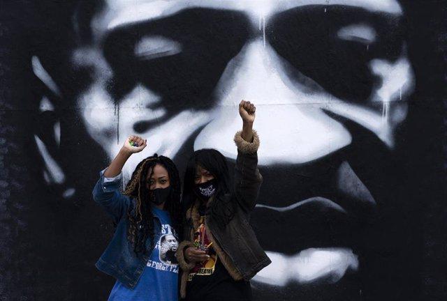 Dos mujeres alzan el puño con un mural de George Floyd a su espalda en la denominada 'Plaza George Floyd' de Mineaopolis, la ciudad donde el afroamericano fue asesinado por la Policía.