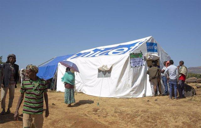 Varias personas hacen cola en una tienda del campo de desplazados de Chagni en Etiopía poco días después de una masacre étnica contra la minoría Ahmara en la región.