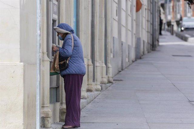 Una mujer protegida con mascarilla y abrigada saca dinero de un cajero de la capital un día marcado por la llegada a la península de una borrasca fría que ha activado la alerta por viento o lluvia en 8 comunidades, entre ellas, Madrid, en los inicios del
