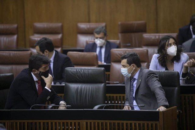 El presidente de la Junta de Andalucía, Juanma Moreno (d), conversa con el vicepresidente de la Junta de Andalucía, Juan Marín (i), durante la primera jornada del Pleno del Parlamento de Andalucía. En Sevilla (Andalucía, España), a 10 de febrero de 2021.