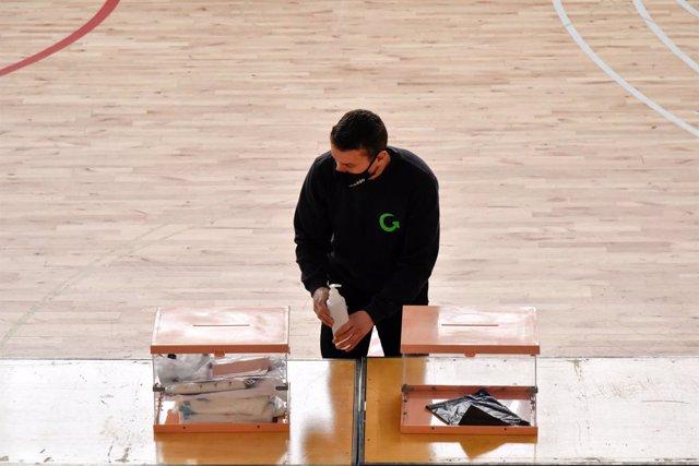 Un treballador al costat de dues urnes en el dispositiu electoral per als comicis catalans d'aquest diumenge