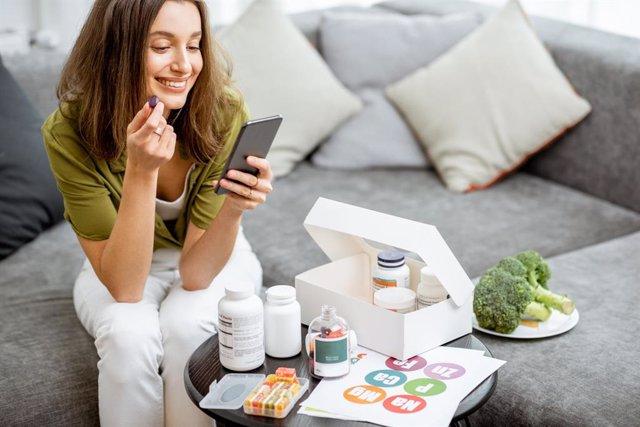 Mujer tomando suplementos vitamínimos.