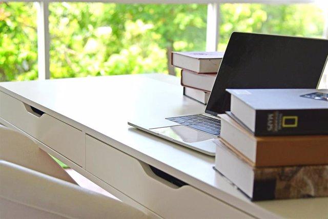 Un escritorio con un ordenador portátil y varios libros