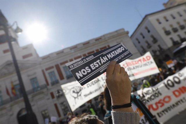Una persona sujeta un cartel en el que se lee: `Nos están matando durante un paseo popular temático en defensa de Madrid y de los servicios públicos organizado por la Coordinadora 25S