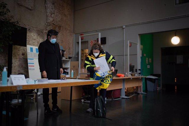 Una treballadora de Correus deixa els vots per correu en una mesa electoral de l'Antic Convent St. Agustí a Barcelona aquest 14F.