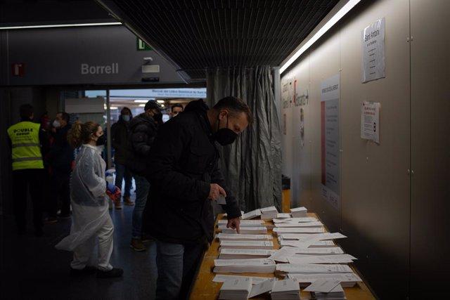 Un home tria la papereta electoral al Mercat St. Antoni a Barcelona