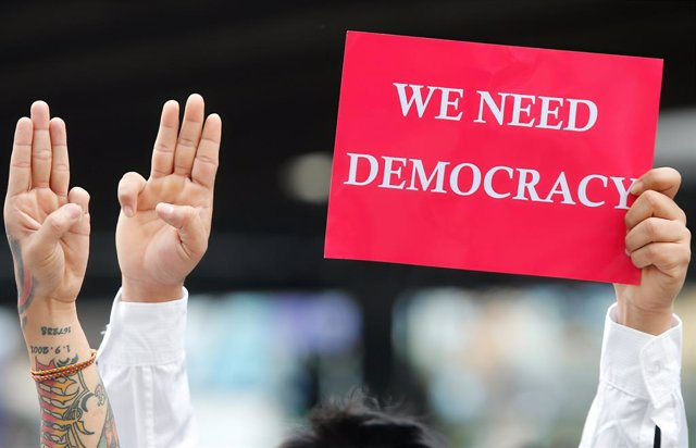 10 February 2021, Thailand, Bangkok: Demonstrators show the three-finger salute, as a sign of resistance and in support of the protests against the military coup in Myanmar  during a rally demanding the prime minister to resign and reforms in the monarchy