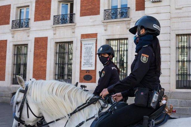 Dos agentes de Policía Nacional a caballo vigilan las inmediaciones de la Puerta del Sol, en Madrid (España), a 9 de octubre de 2020. El Ministerio del Interior ha comenzado a desplegar un amplio operativo de controles policiales en Madrid y el resto de m