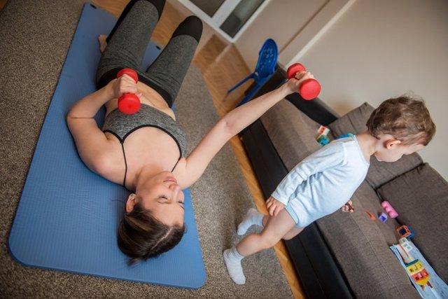 Mujer en plena pandemia haciendo ejercicio en casa junto a su hijo.