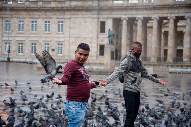 08 January 2021, Colombia, Bogota: Two men play with the pigeons in Bolivar Square. Bogota enters in a 4-day strict quarantine due to the spread of the coronavirus pandemic. Photo: Chepa Beltran/VW Pics via ZUMA Wire/dpa