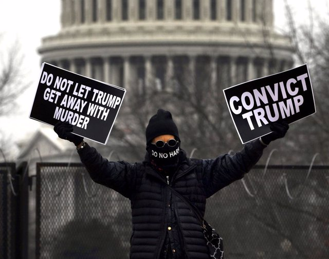 13 February 2021, US, Washington: A protester hold signs near Union Station during the fifth day of the second impeachment trial of US President Trump in the Senate. Photo: Carol Guzy/ZUMA Wire/dpa