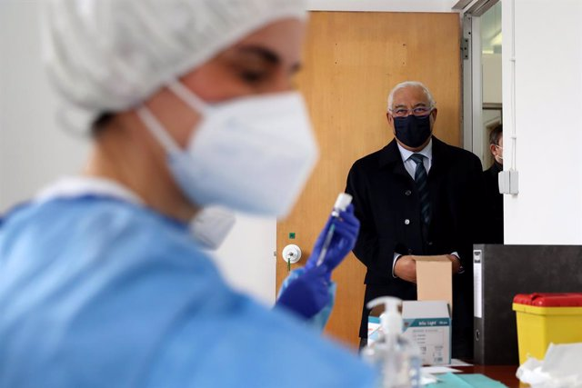 13 February 2021, Portugal, Lisbon: Portuguese Prime Minister Antonio Costa looks on as health technicians fill up syringes with a dose of the AstraZeneca Covid-19 vaccine on the first day of the security forces inoculation at the Conde de Lippe military