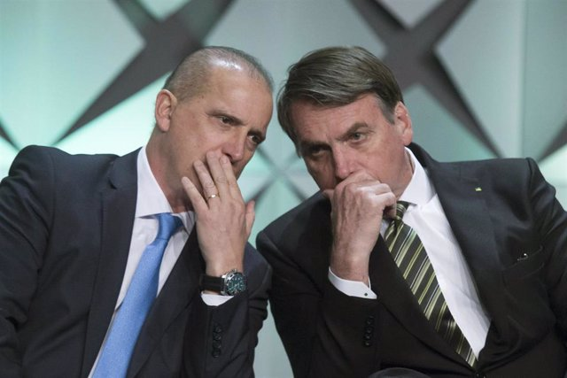 El nuevo secretario general de la Presidencia de Brasil, Onyx Lorenzoni, susurra al oído del presidente del país, Jair Bolsonaro, en una imagen de archivo.