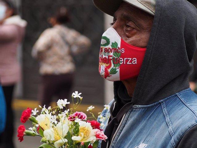 Un ciudadano peruano con una mascarilla con la bandera del país.