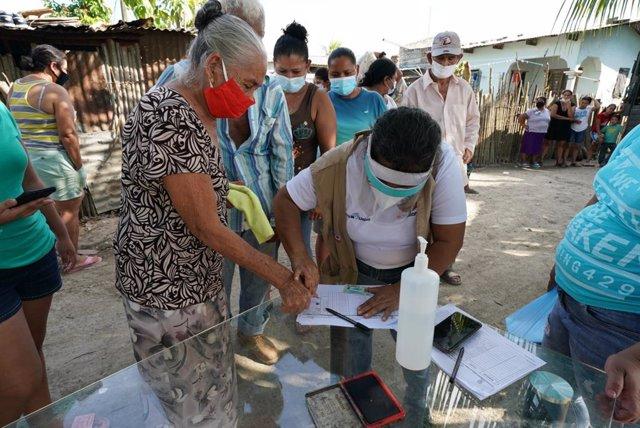 Un trabajador humanitario hondureño utiliza una huella dactilar para registrar a un residente de la comunidad Brisas de la Bueso cerca de Choloma, Honduras, para recibir suministros de socorro.