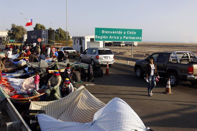 25 June 2019, Chile, Arica: Migrants from Venezuela lie on the ground in front of a border checkpoint, waiting for the visa to enter Chile. Photo: Alexander Infante/Agencia Uno/dpa