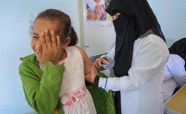 Una cooperant d'UNICEF vacuna una nena contra la rubèola i el xarampió a Iemen