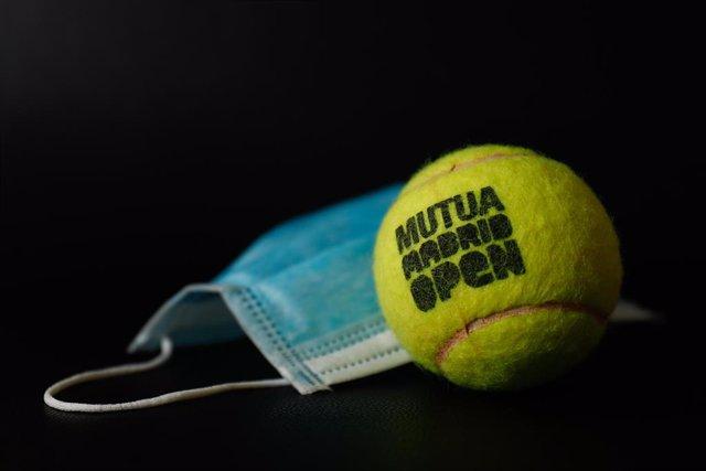 Una bola oficial del torneo de tenis profesional Mutua Madrid Open junto a una máscara quirúrgica, en Valdemoro (Comunidad de Madrid/España) a 26 de abril de 2020. La competición se 'jugará' de forma virtual del 27 al 30 de abril desde los domicilios de l