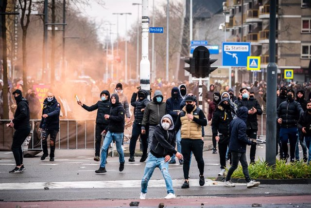 24 January 2021, Netherlands, Eindhoven: Demonstrators throw stones towards the police during a demonstration against the current Corona policy in front of the Eindhoven Railway station. Photo: Rob Engelaar/ANP/dpa