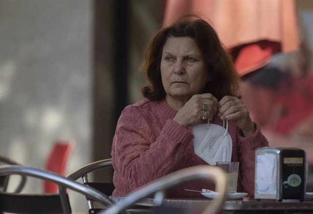 Una mujer en la terraza de un bar con la mascarilla en la mano, mientras continúa el cierre perimetral en Montequinto (Dos Hermanas), al entrar en nivel 4 de alerta  desde el pasado 20 de enero cuando superó la tasa de incidencia de Covid-19 de 500 casos