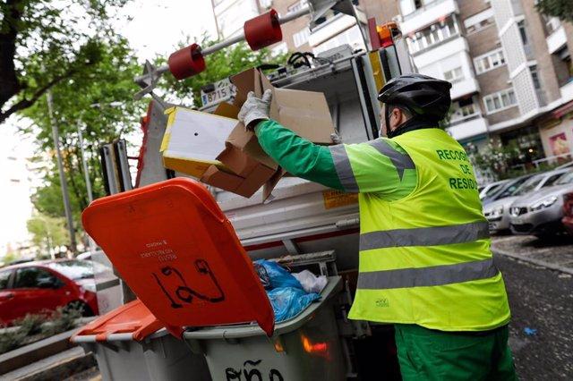 Un operario de recogida de residuos protegidos con mascarilla extrae cajas de cartón de un cubo de basura para triturarlas en un camión de basura durante su trabajo de limpieza en una calle de la capital durante el día 33 del estado de alarma, en Madrid (