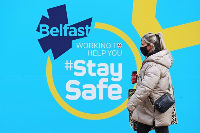 12 January 2021, Northern Ireland, Belfast: A woman wears a face mask walks past a public information sign in Belfast as Northern Ireland remains in an extended lockdown to curb the spread of coronavirus and lower infection rates. Photo: Liam Mcburney/PA