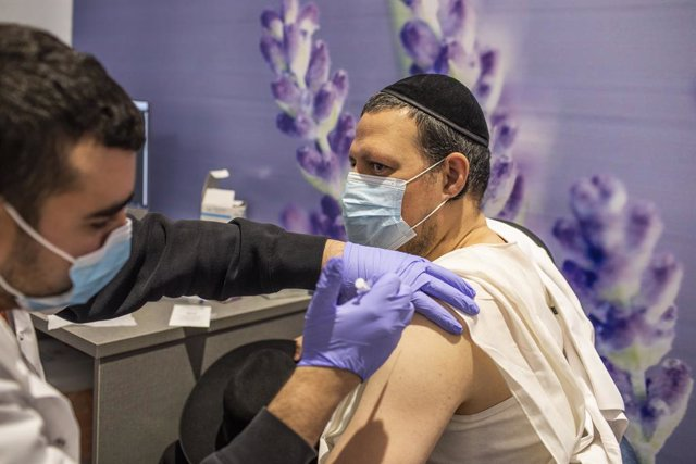 11 January 2021, Israel, Jerusalem: An Orthodox Jewish man receives his dose of the Pfizer-BioNTech COVID-19 vaccine at a vaccination centre as a part of a nationwide campaign. Israeli Health Minister Yuli Edelstein earlier said that Israel has vaccinated