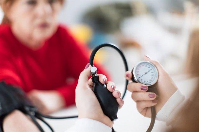 Midiendo la presión arterial a una paciente.