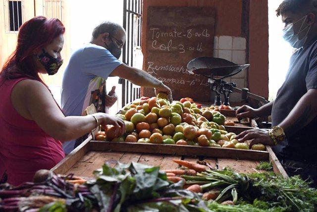 Varias personas compran en una frutería en La Habana.