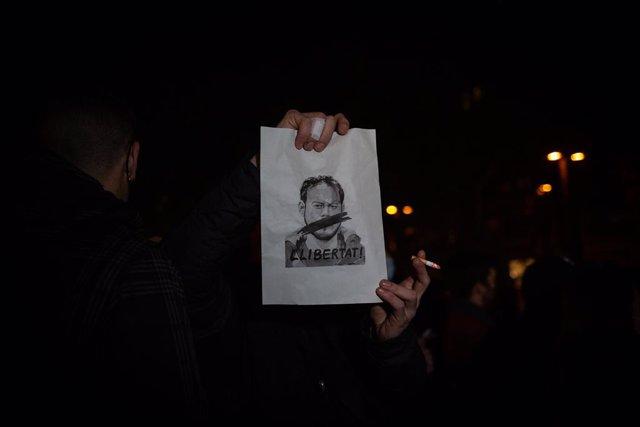 Un home subjecta un cartell en què es veu la cara de Pablo Hasel i `llibertat durant una concentració en rebuig a l'empresonament de Pablo Hasel en la plaça Lesseps a Barcelona, Catalunya (Espanya), a 16 de febrer de 2021