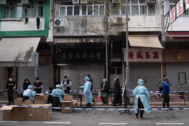 20 January 2021, China, Hong Kong: Health workers assist people queuing up for their coronavirus (Covid-19) tests at a mobile testing site. Photo: Geovien So/SOPA Images via ZUMA Wire/dpa