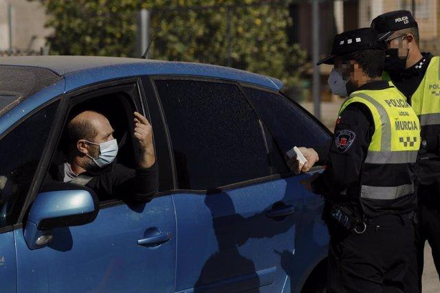 Dos policías locales en un control situado en el límite entre los municipios de Murcia y Santomera, en Murcia (España) a 13 de febrero de 2021.