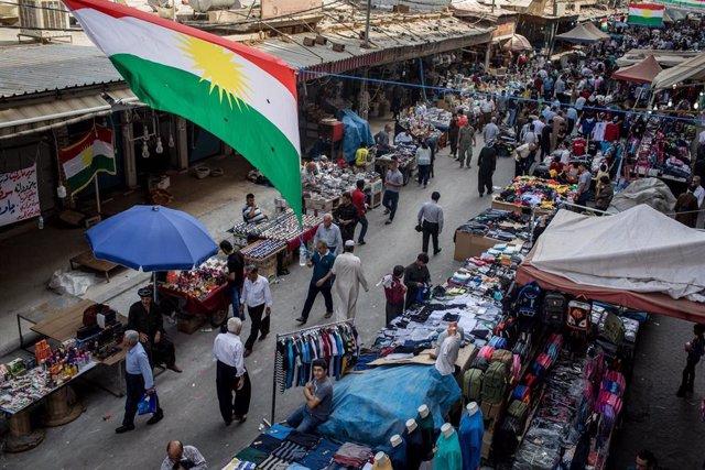 Un mercado de la ciudad de Erbil, en el Kurdistán iraquí, con una bandera del Kurdistán