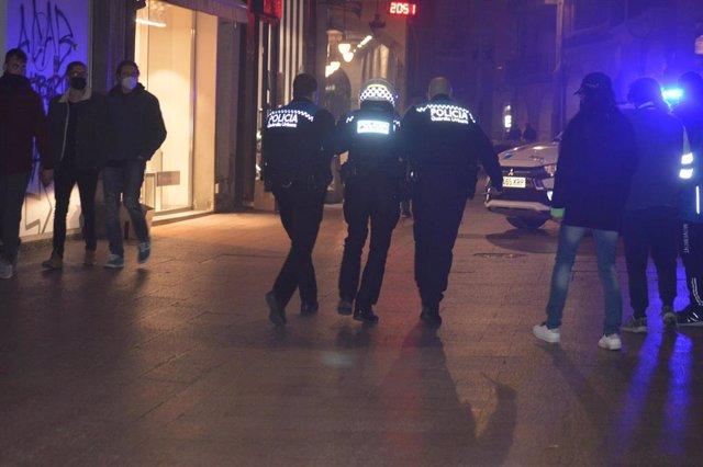 Dos agentes de la Policía Local de Lleida trasladan al edificio del Ayuntamiento a un compañero herido este martes.
