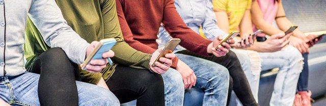 Imágenes de recurso de jóvenes usando teléfonos móviles