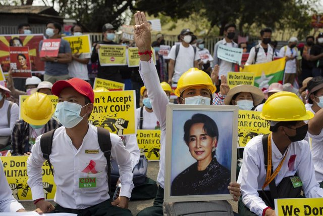 18 February 2021, Myanmar, Yangon: A protester holds a portrait of Aung San Suu Kyi and makes a three-finger salute during a protest against the military coup. Photo: Aung Kyaw Htet/SOPA Images via ZUMA Wire/dpa