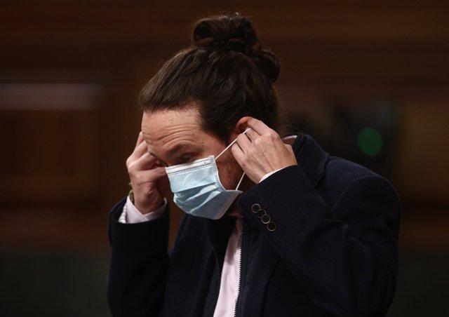 El secretario general de Podemos y vicepresidente segundo del Gobierno, Pablo Iglesias, se coloca la mascarilla durante una sesión de Control al Gobierno celebrada en el Congreso de los Diputados