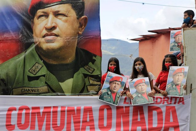 04 February 2021, Venezuela, Caracas: Children, along with a picture of the late President Hugo Chavez, take part in a march to commemorate the military uprising of 4 February 1992, in the 23 de Enero neighbourhood. Photo: Jesus Vargas/dpa