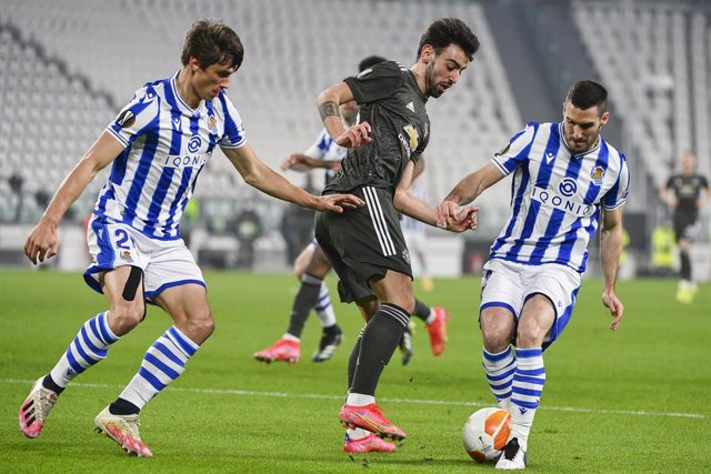 18 February 2021, Italy, Turin: Manchester united's Bruno Fernandes (C) battles for the ball with Real Sociedad's Robin Le Normand and Joseba Zaldua during the UEFA Europa League round of 32 first leg soccer match between Real Sociedad and Manchester Unit