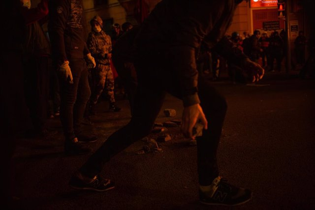 Encaputxats llancen pedres i cremen contenidors en la tercera nit de disturbis a Barcelona en protesta per l'empresonament de Pablo Hasel, el 18 de febrer de 2021.