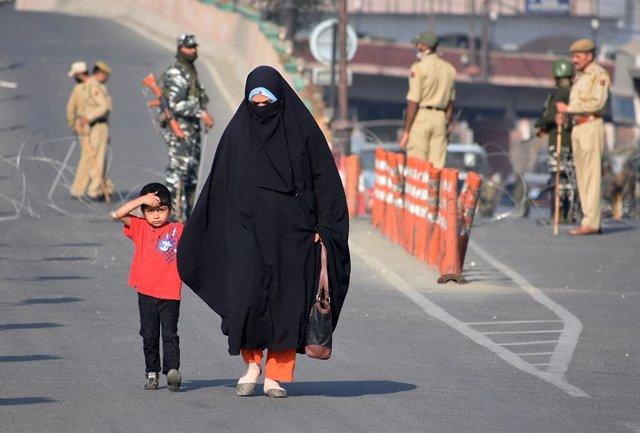 Archivo - Una mujer con su hijo cerca de un puesto de control militar en la Cachemira india
