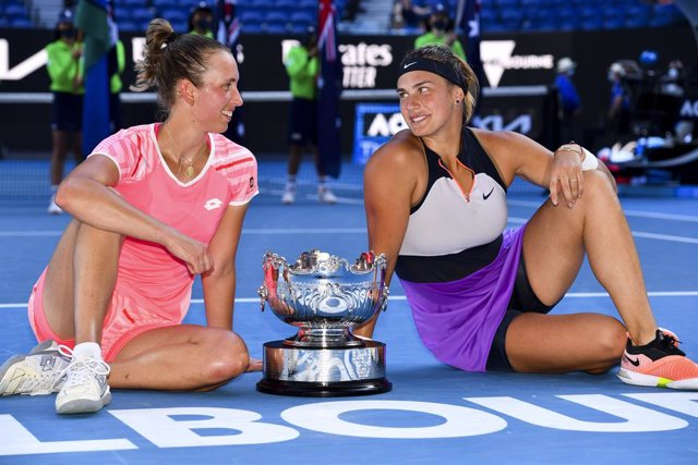 Elise Mertens of Belgium (left) and Aryna Sabalenka of Belarus pose for photographs with the trophy after winning their Women's Doubles Finals match against Barbora Krejcikova of the Czech Republic and Katerina Siniakova of the Czech Republic on Day 12 of