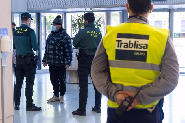 Agentes de la Guardia Civil y empleados de seguridad vigilan a los pasajeros en el interior del Aeropuerto de Ibiza